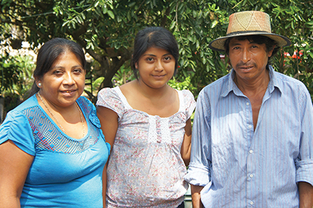 Maria Torres Tzab, Fatima Castillo Torres and Nicolas Castillo Ucam stand outside their home in Mani.